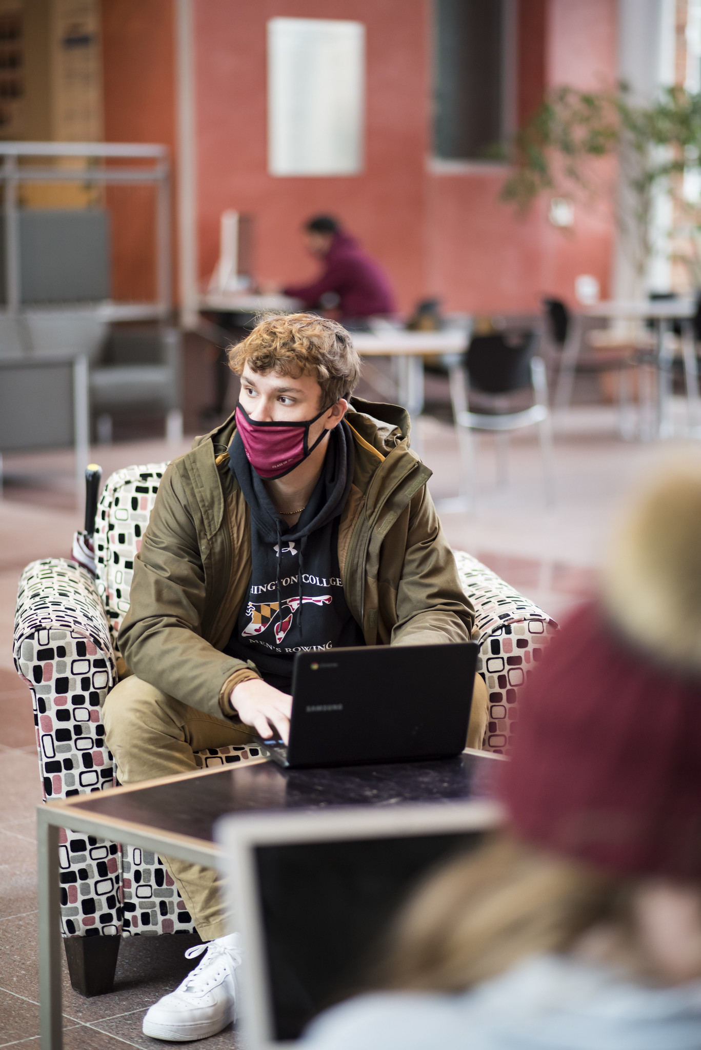 student with mask at laptop