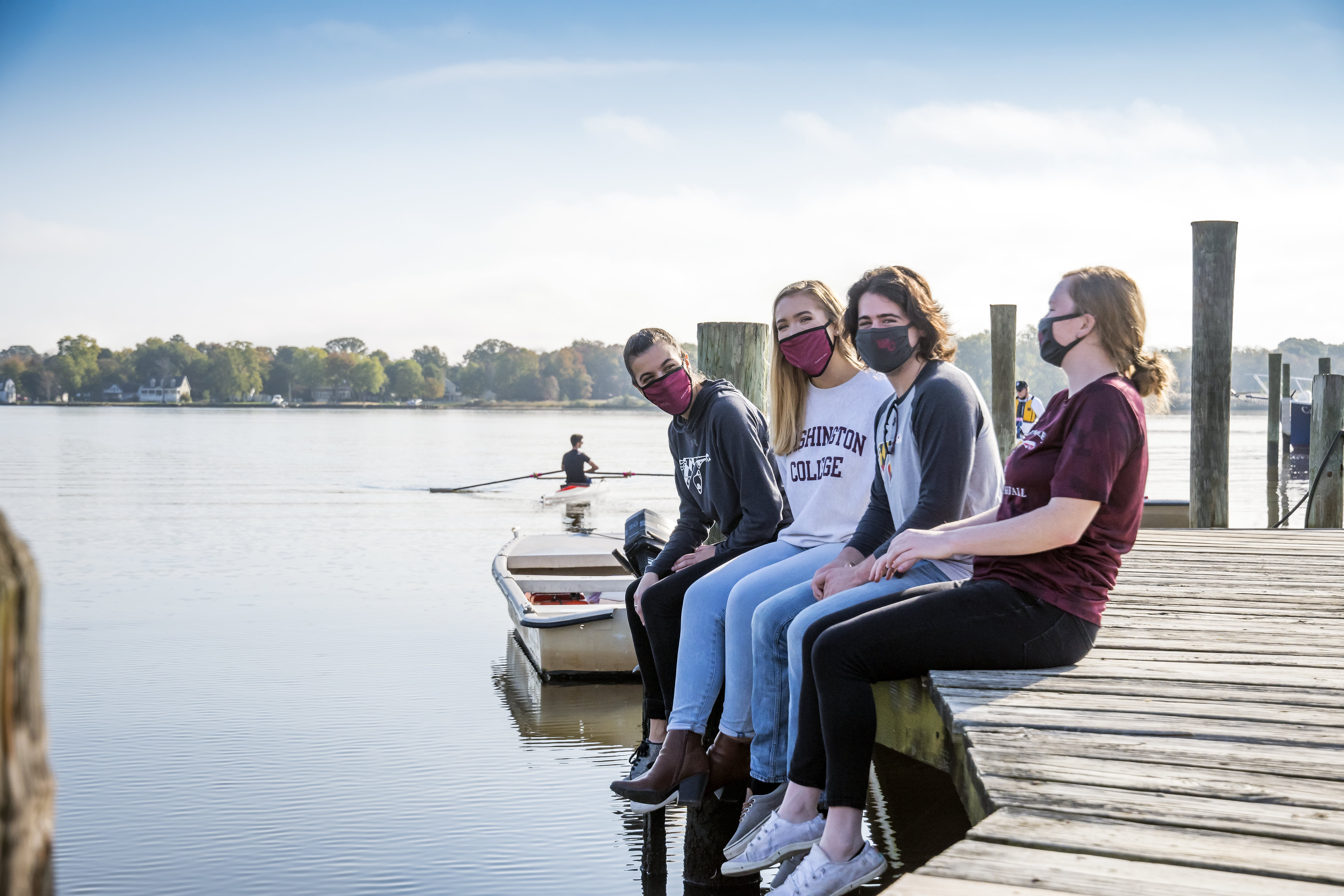 Several masked Washington College students sitting on the dock of our riverfront campus.